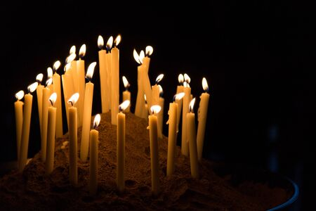 Many candles give warm yellow light in black background