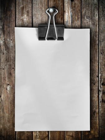Black clip and White blank note paper hang on wood panel