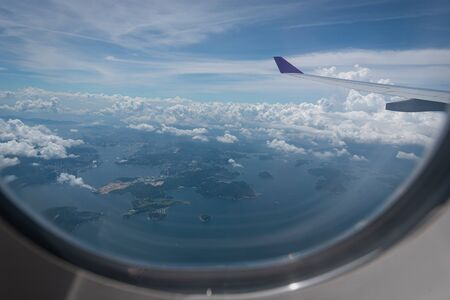 Photo pour Wing of airplane flying above Hong Kong city background through the window. - image libre de droit