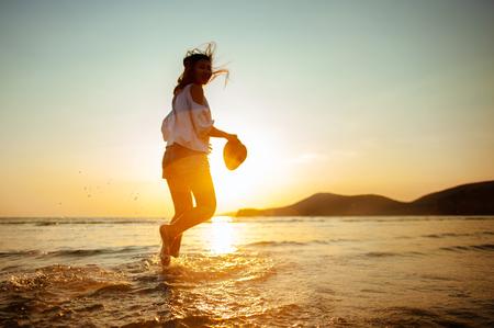Photo for Woman Enjoying Beautiful Sunset on the Beach - Royalty Free Image