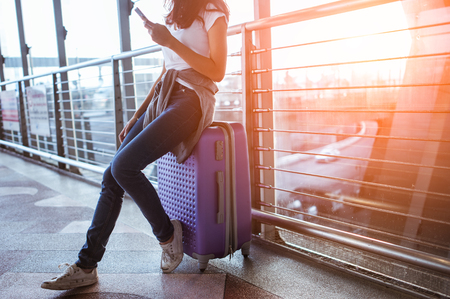 Photo pour girls using smartphone checking flight or online check-in at airport together, with luggage. Air travel, summer holiday, or mobile phone application - image libre de droit