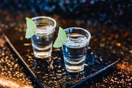 Photo pour Gin or vodka with lime. Two glasses with a cocktail alcohol with lemons on the black blue surface. Vodka, cocktail, alcohol, beverage, restaurant, relax concept. - image libre de droit