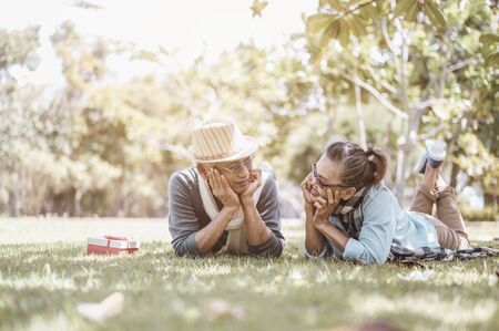 Photo pour Senior, couples, retirement, insurance, elderly, lifestyle concept.  Senior couples sitting and talking on the outdoor lawn in the morning about life insurance plans with a happy retirement concept. - image libre de droit