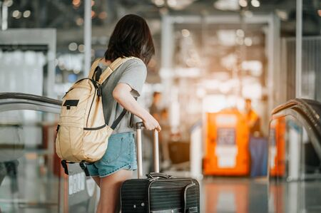 Photo pour Young woman pulling suitcase in modern airport terminal. Travelling guy with his luggage while waiting for transport. Rear view. Copy space - image libre de droit