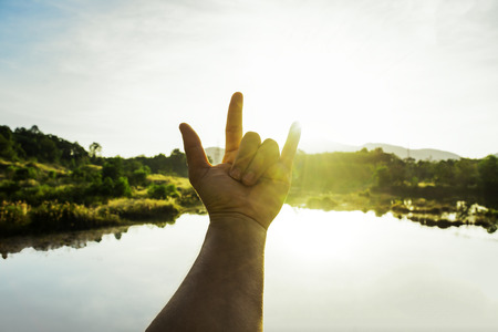 Photo for Use hand to touch the sun light in the morning, Love sign, Yellow light with cold air, Flare light from sunrise, holding sun rays, Symbols of hope, pray for god - Royalty Free Image