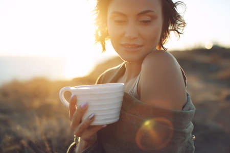 Photo for Beautiful woman drinks coffee. Woman outdoors. High quality photo. - Royalty Free Image