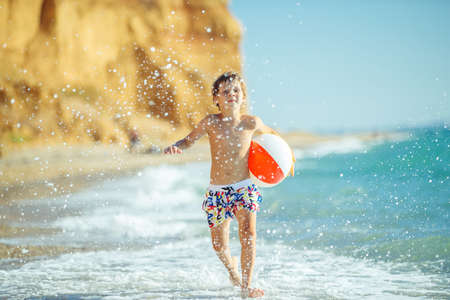 Photo for Boy child has fun at sea. Summer, happiness, sea and a child with a ball. High quality photo. - Royalty Free Image