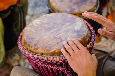 Man playing the djembe (african drum) outdoors