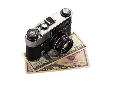 Old vintage camera with dollars isolated on white background.