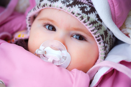 Photo for A few months old baby outdoor in warm clothes in a cold winter day. - Royalty Free Image