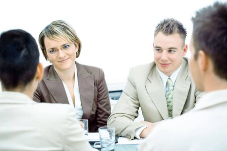 Happy young businesspeople talking on meeting at office.