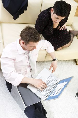 Businessman sitting on floor and teamworking on laptop computer with businesswoman. They look workoholic. High-angle view.