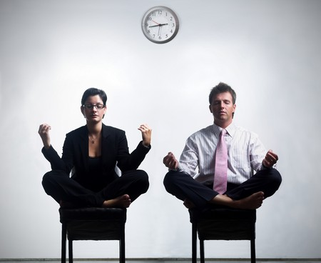 Young business people in an abstract office enviroment are sitting in yoga lotus-pose and relaxing.