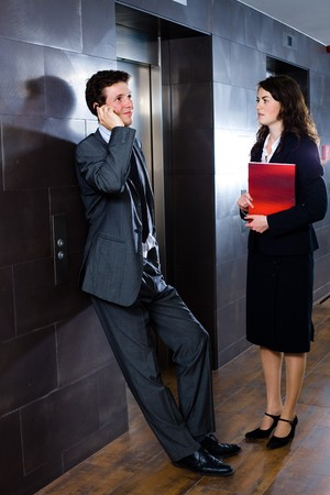 Young businesspeople waiting at office lobby, businessman calling on phone, businesswoman holding red document folder.