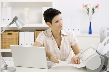 Photo for Woman using fax machine at home office. - Royalty Free Image
