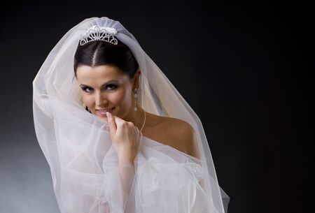 Portrait of a smiling young bride wearing a white wedding dress, holding her veil lloking at camera.