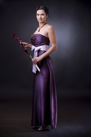 Studio portrait of a beautiful young woman wearing a light purple evening dress holdiing flowers in her hands.