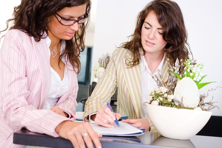 Casual businesswomen working together in team at office reception, looking at documents, talking.