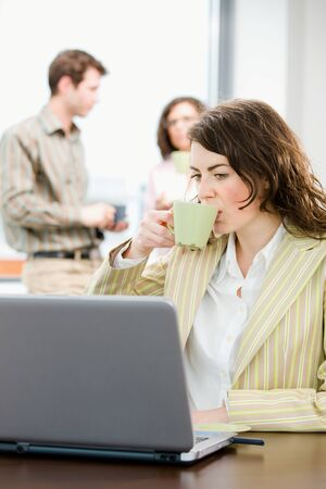 Team of young successful office workers talking and drinking coffee at meeting room, businesswoman working on laptop computer in front.