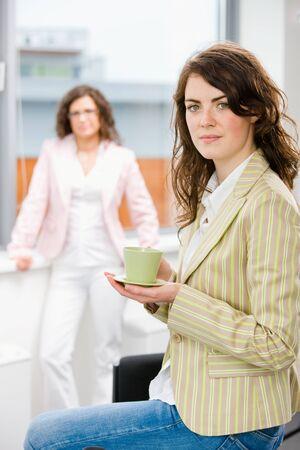 Young businesswomen having break at office drinking coffee.