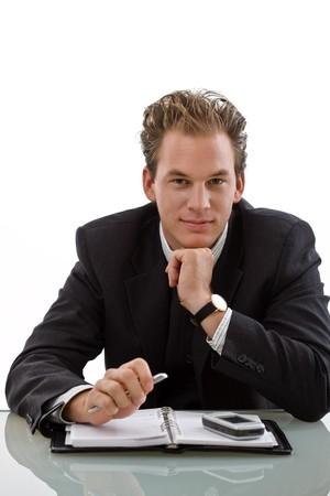 Smiling businessman working at desk, white background.