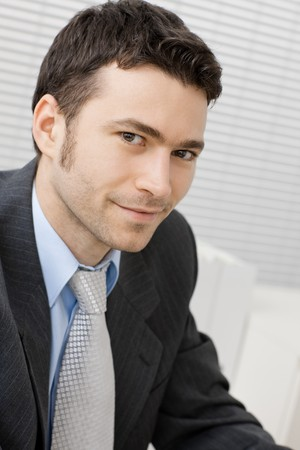 Portrait of happy smiling young businessman at office.