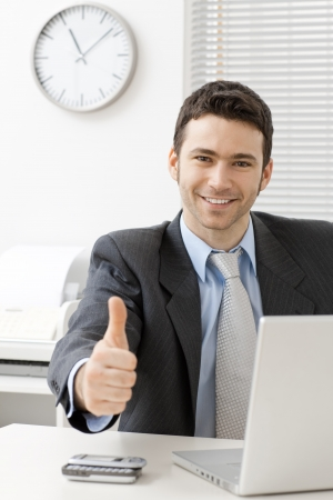 Happy young businessman showing success with thumb up at office, smiling.の写真素材