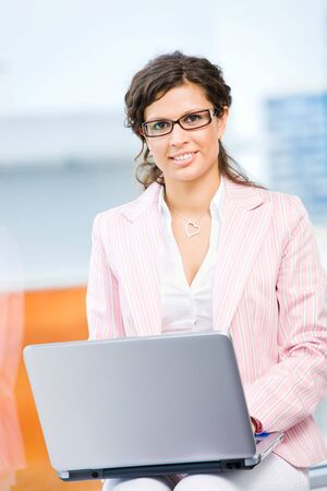 Young happy businesswoman working on laptop computer in fron front of office window, smiling.