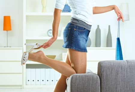 Woman taking off high heel shoe at home, holding shopping bag.