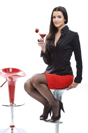 Sexy young woman sitting on bar chair, holding glass of cocktail in hand.