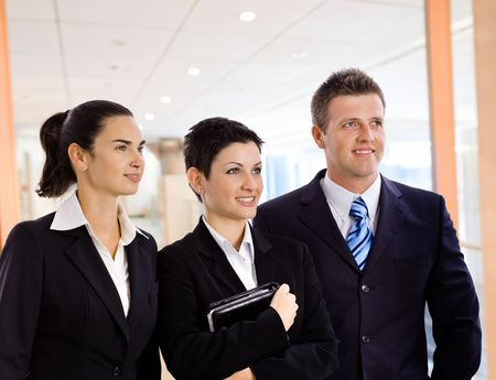 Young business team standing in corporate office lobby.
