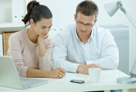 Photo for Happy young casual couple sitting  at desk working together at home office, smiling. - Royalty Free Image