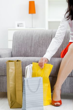 Young woman sitting on couch after day of shopping, surrounded with colorful shopping bags.
