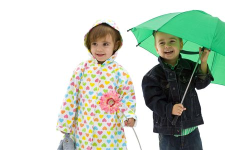 Happy laughing children. Boy holding a green umbrella. Girl wearing raincoat and holding flower. Isolated on white background.の写真素材