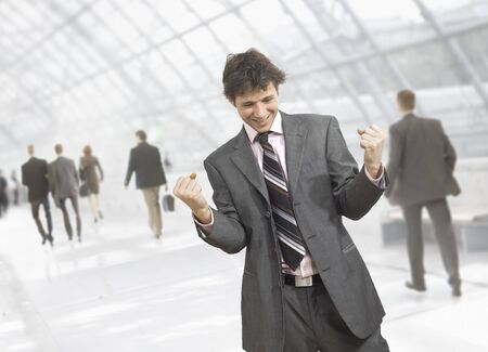 Happy young businessman celebrating business success with fists clenched, smiling.  Isolated on white.