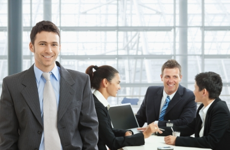 Happy businessman standing in front, businesspeople talking at desk in the background.