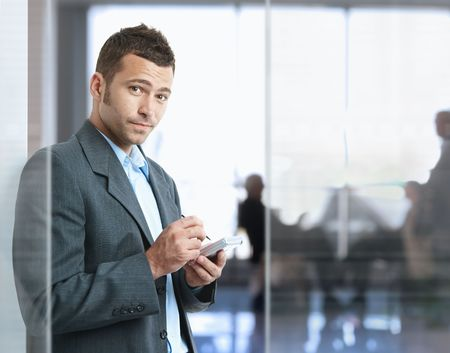 Serious businessman standing in office lobby , using smart phone, looking at camera.