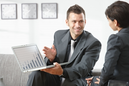 Young businessman showing financial graph to partner at office, smiling.
