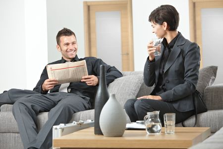Business people sitting on sofa at office anteroom waiting and talking