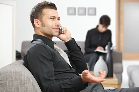 Young businessman sitting at office lobby talking on mobile phone.