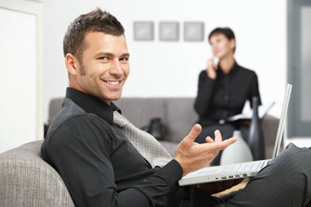 Young businessman sitting at office lobby working with laptop computer, smiling.