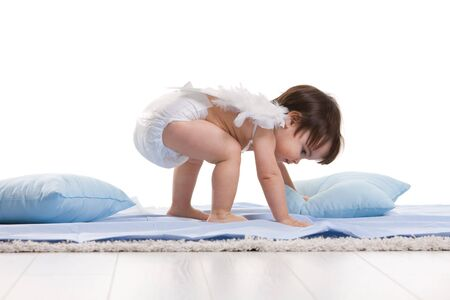 Photo pour Baby girl wearing white angel wings, playing with blue pillows. Isolated on white background. - image libre de droit
