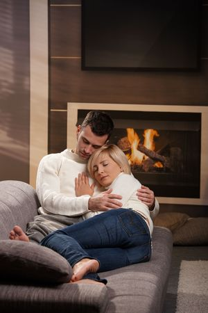 Young couple hugging on sofa in front of fireplace at home, eyes closed.