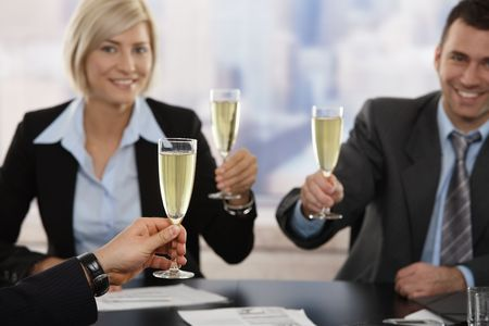 Happy young business people sitting around meeting table at office raising toast with champagne, smiling. Focus placed on hand in front.