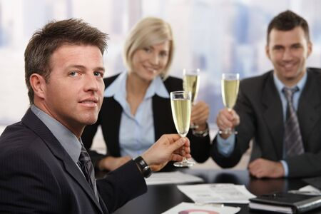 Happy middle-aged businessman sitting at meeting table at office celebrating success with champagne, smiling.