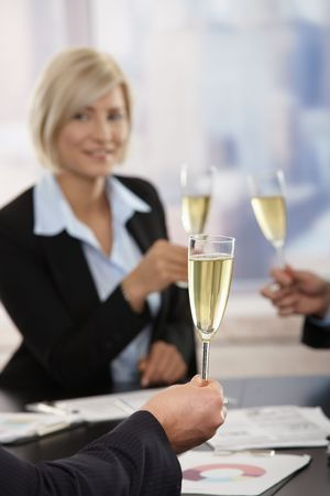 Business people raising toast with champagne flutes over meeting table at office. Focus placed on hand in front.