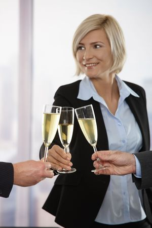 Business people celebrating success, raising toast with champagne. Focus placed on flutes.