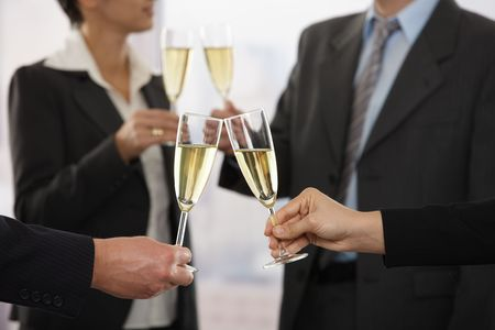 Business people raising toast with champagne at office, focus placed on flutes.