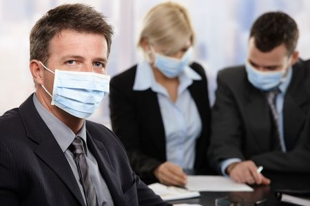 Businessman fearing h1n1 swine flu virus wearing protective face mask during meeting at office.