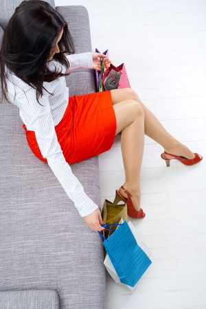 Young woman sitting on couch after day of shopping, packing colorful shopping bags. Overhead shot.